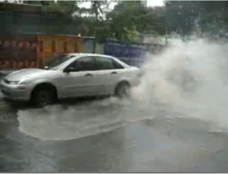 gejzer z miejskiej kanalizacji podrywa auto do góry