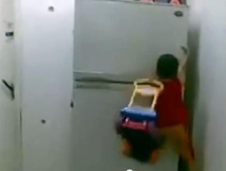 Dziecko - pająk wspina się po lodówce